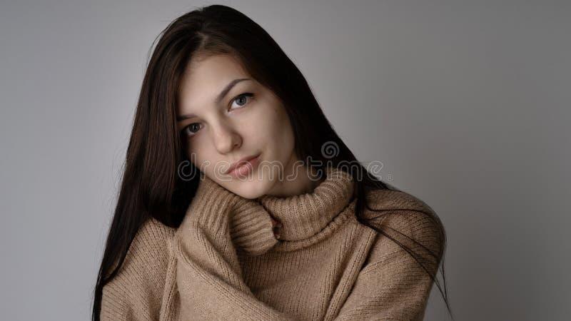Giovane donna castana splendida in maglione tricottato caldo su fondo grigio chiaro immagini stock libere da diritti