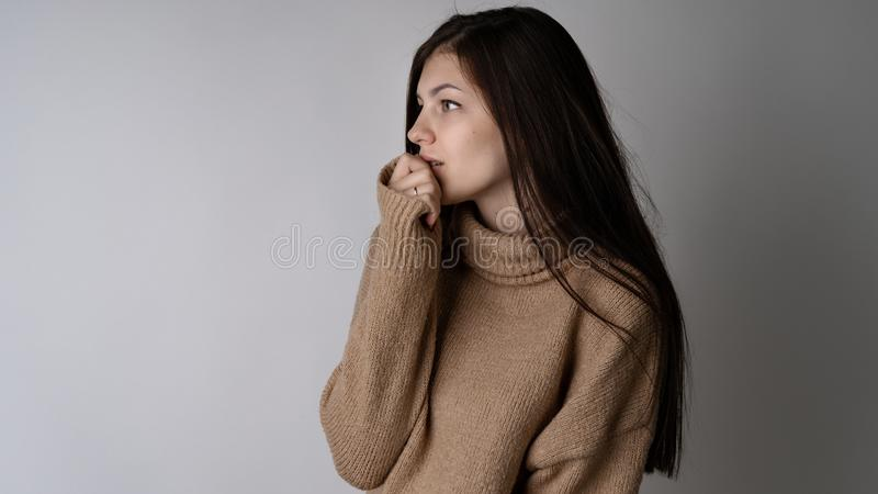 Giovane donna castana splendida in maglione tricottato caldo su fondo grigio chiaro immagini stock