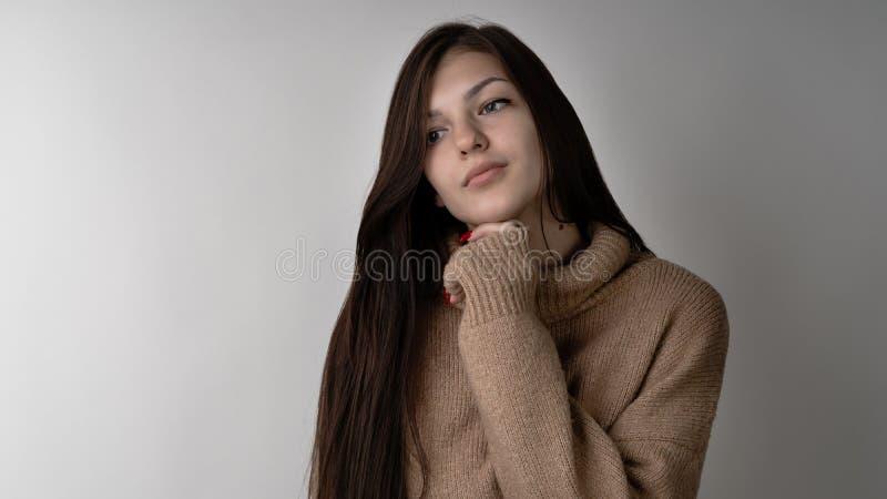 Giovane donna castana splendida in maglione tricottato caldo su fondo grigio chiaro fotografia stock libera da diritti