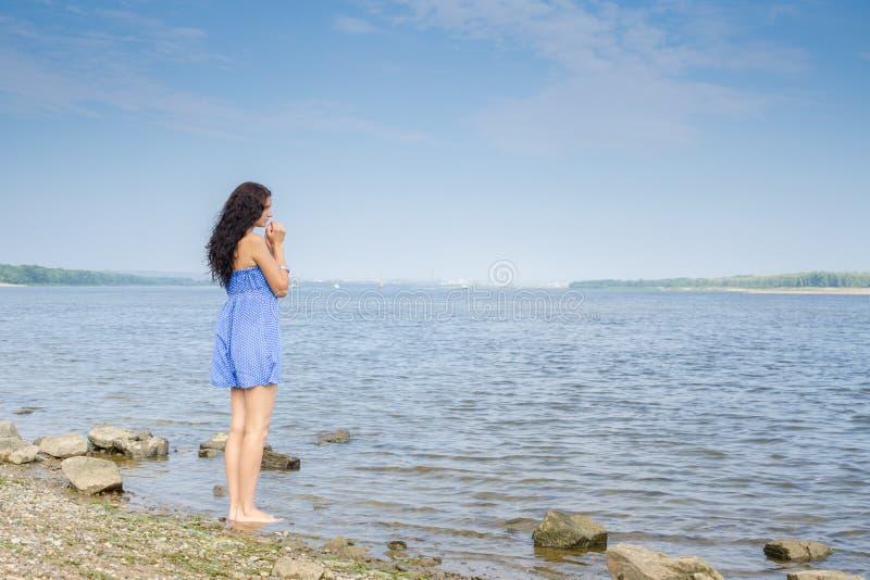 Giovane donna castana triste in vestito blu da estate che sta sulla sponda del fiume immagine stock