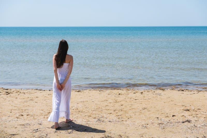 Giovane donna castana in vestito bianco da estate che sta sulla spiaggia e che guarda al mare immagini stock