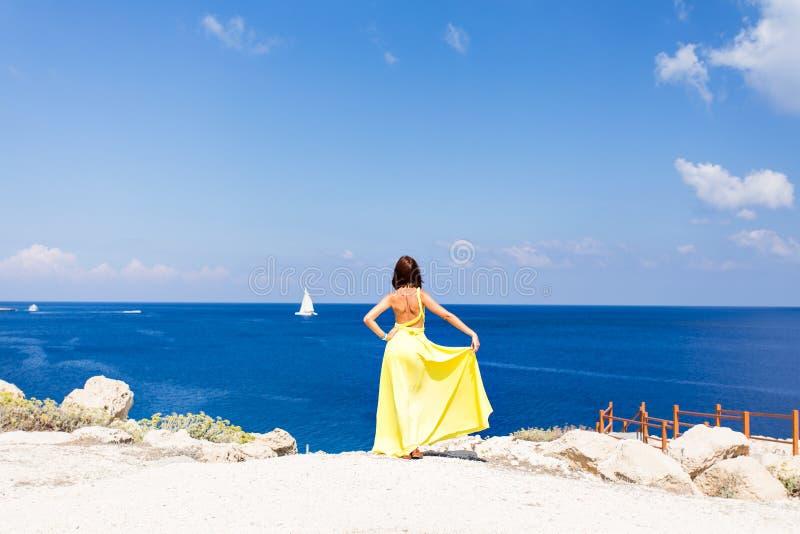 Giovane donna castana in vestito da giallo di estate che sta sulla spiaggia e che guarda al mare fotografia stock