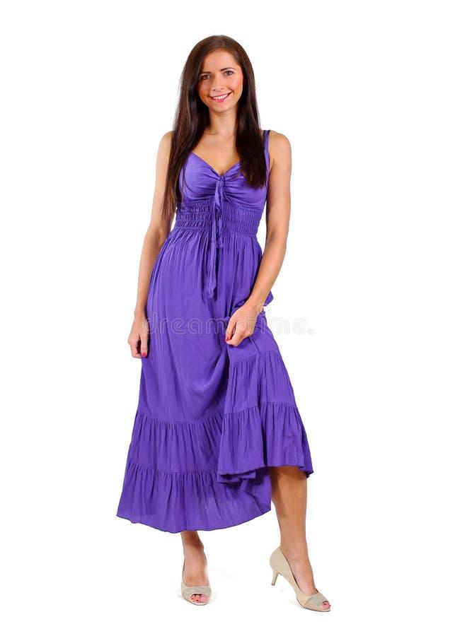 Giovane donna castana in vestito porpora/viola isolato su fondo bianco immagine stock libera da diritti