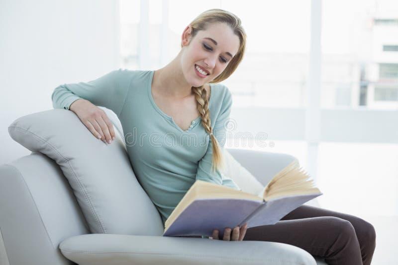 Giovane donna casuale che legge un libro mentre sedendosi sorridere sullo strato immagini stock libere da diritti