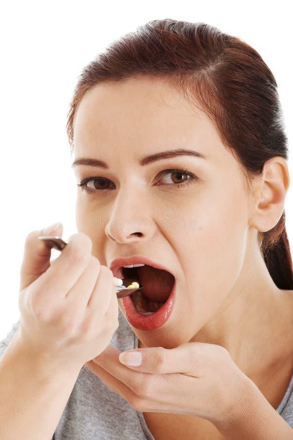 Giovane donna casuale che mangia le pillole su un cucchiaio. immagini stock