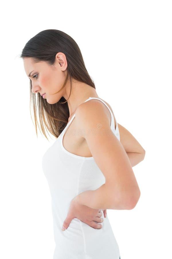 Giovane donna casuale che soffre dal dolore alla schiena fotografia stock libera da diritti