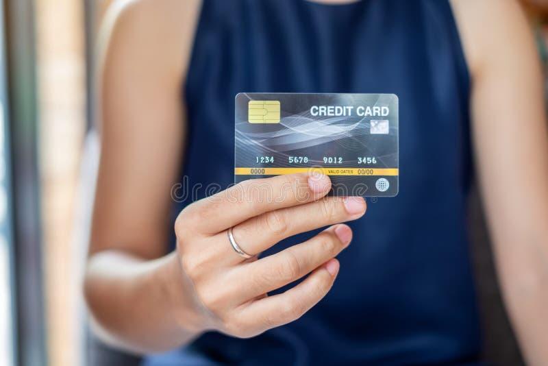 Giovane donna casuale di affari che tiene la carta di credito per acquisto online mentre facendo gli ordini nel caffè affare, sti fotografia stock libera da diritti