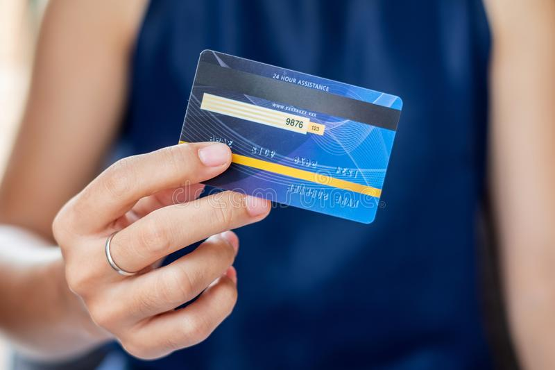 Giovane donna casuale di affari che tiene la carta di credito per acquisto online mentre facendo gli ordini nel caffè affare, sti fotografia stock