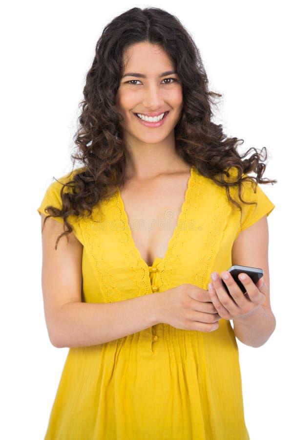Giovane donna casuale sorridente che invia messaggio di testo fotografie stock