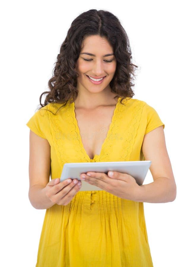Giovane donna casuale sorridente che per mezzo del suo computer della compressa fotografia stock libera da diritti