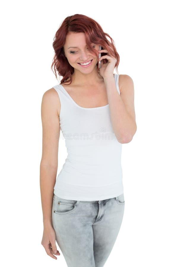 Giovane donna casuale sorridente che per mezzo del telefono cellulare immagini stock