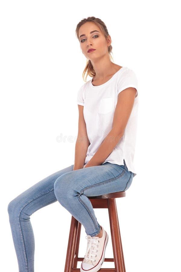 Giovane donna casuale triste che si siede sulla sedia fotografie stock libere da diritti