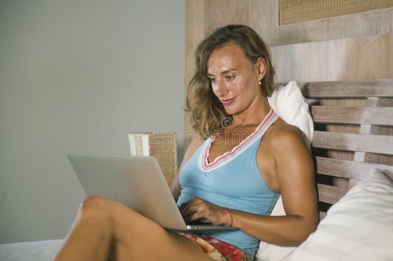 Giovane donna caucasica attraente e bella alla moda 30s che si siede sul letto alla notte in camera da letto domestica facendo us fotografie stock libere da diritti