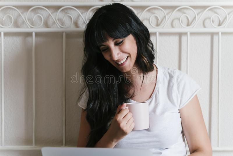 Giovane donna caucasica a casa a letto che mangia una tazza di caffè o un tè Lavorando al computer portatile Mattina e rilassarsi fotografia stock libera da diritti