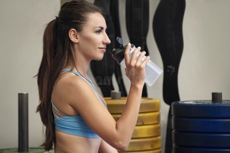 Giovane donna caucasica che sorride e che giudica una bottiglia di plastica riutilizzabile pronta a bere dopo un allenamento inte fotografia stock libera da diritti