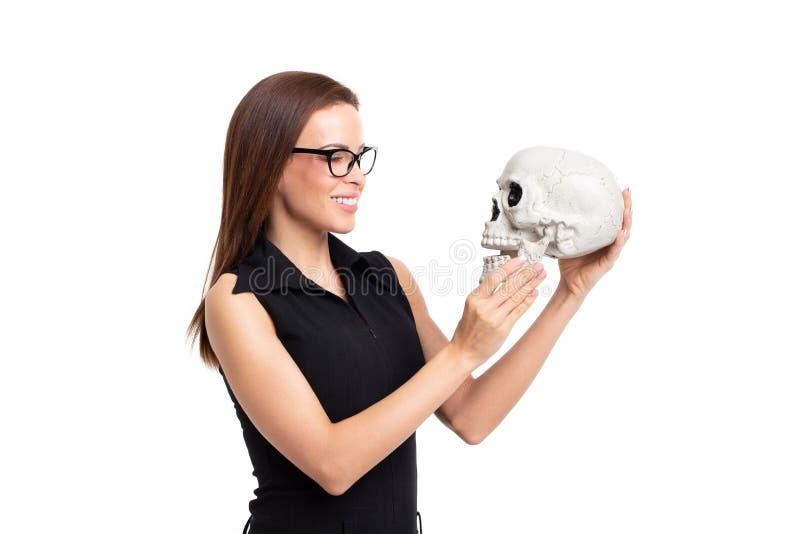 Giovane donna caucasica che sorride sul cranio isolato su bianco immagini stock libere da diritti