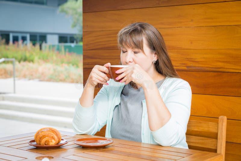 Giovane donna caucasica con capelli lisci che beve tè in un bar immagini stock libere da diritti