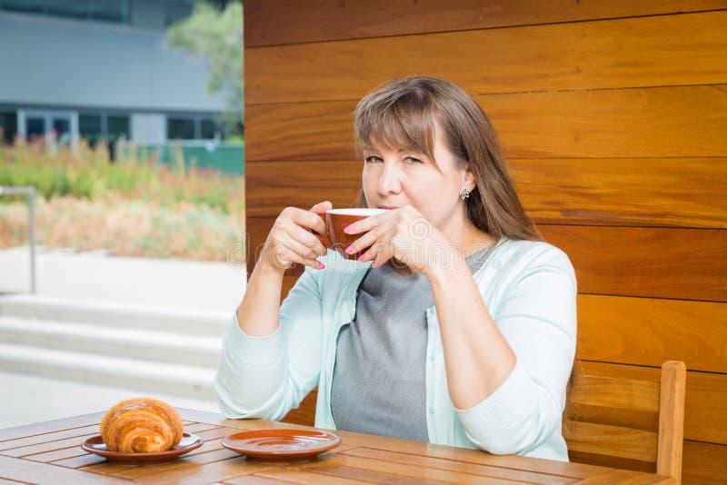 Giovane donna caucasica con capelli lisci che beve tè in un bar immagine stock