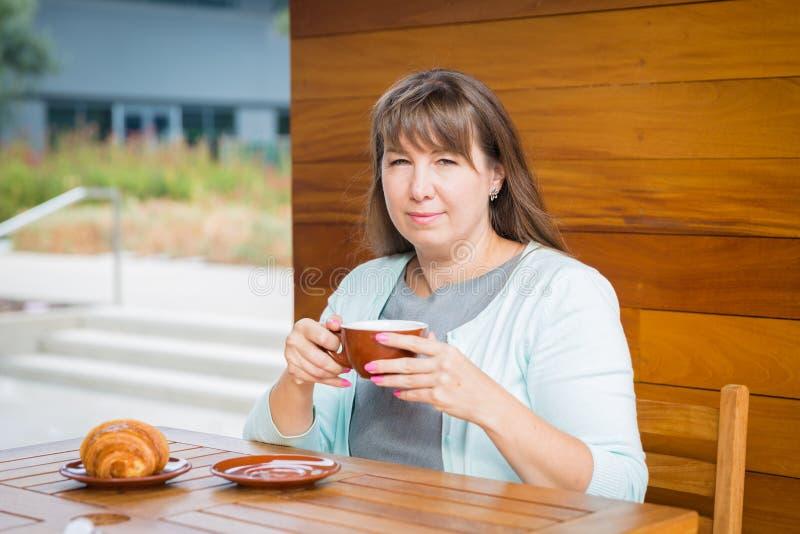 Giovane donna caucasica con capelli lisci che beve tè in un bar fotografia stock libera da diritti
