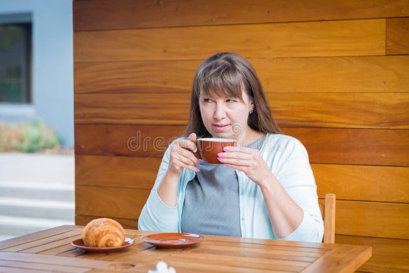 Giovane donna caucasica con capelli lisci che beve tè in un bar fotografie stock libere da diritti