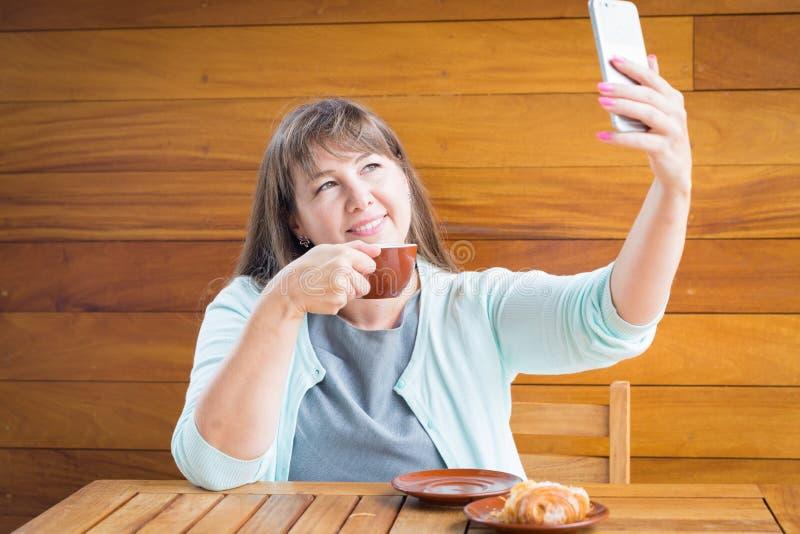Giovane donna caucasica con capelli lisci che beve tè in un bar immagine stock libera da diritti