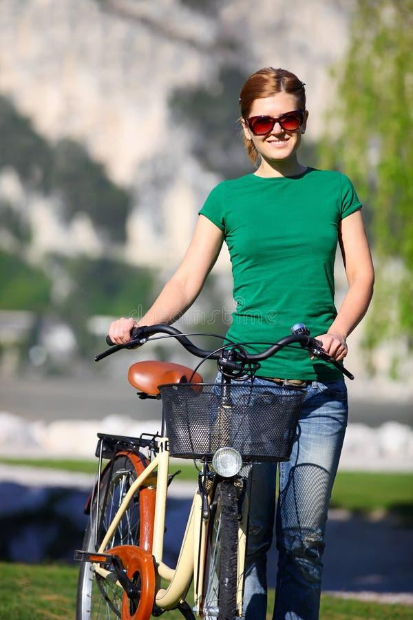 Giovane donna caucasica con la sua bici fotografia stock libera da diritti