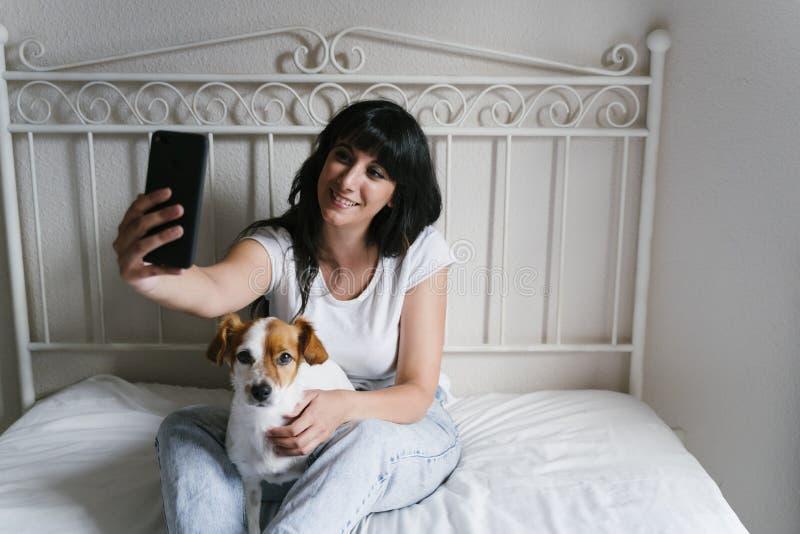 Giovane donna caucasica sul letto che prende un selfie con il telefono cellulare con il suo piccolo cane sveglio Amore per gli an fotografia stock libera da diritti