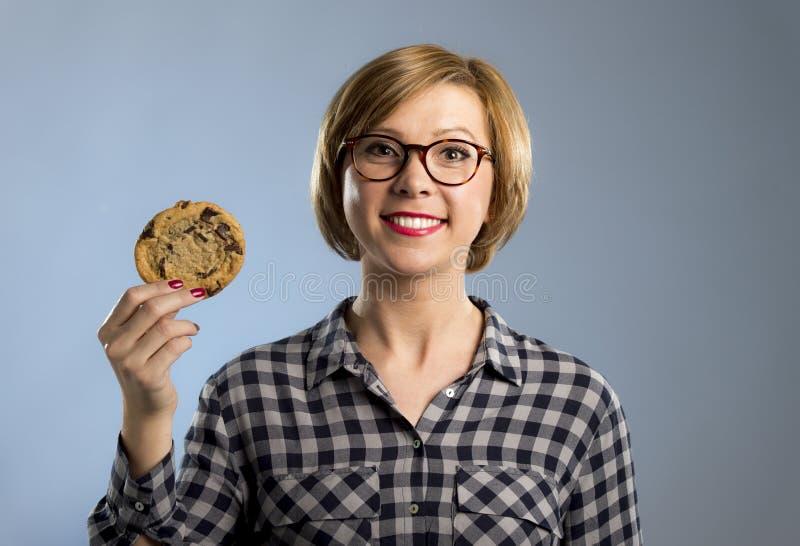 Giovane donna caucasica sveglia ed amichevole bionda in abbigliamento casual che tiene il grande biscotto delizioso del cioccolat immagine stock