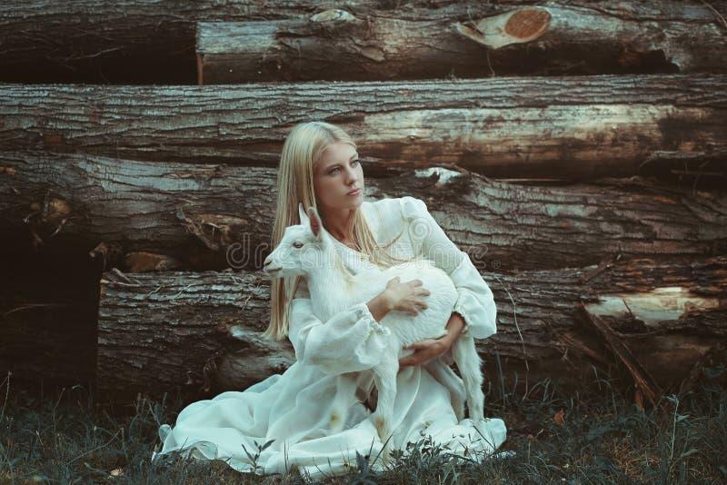 Giovane donna che abbraccia piccola capra fotografie stock libere da diritti