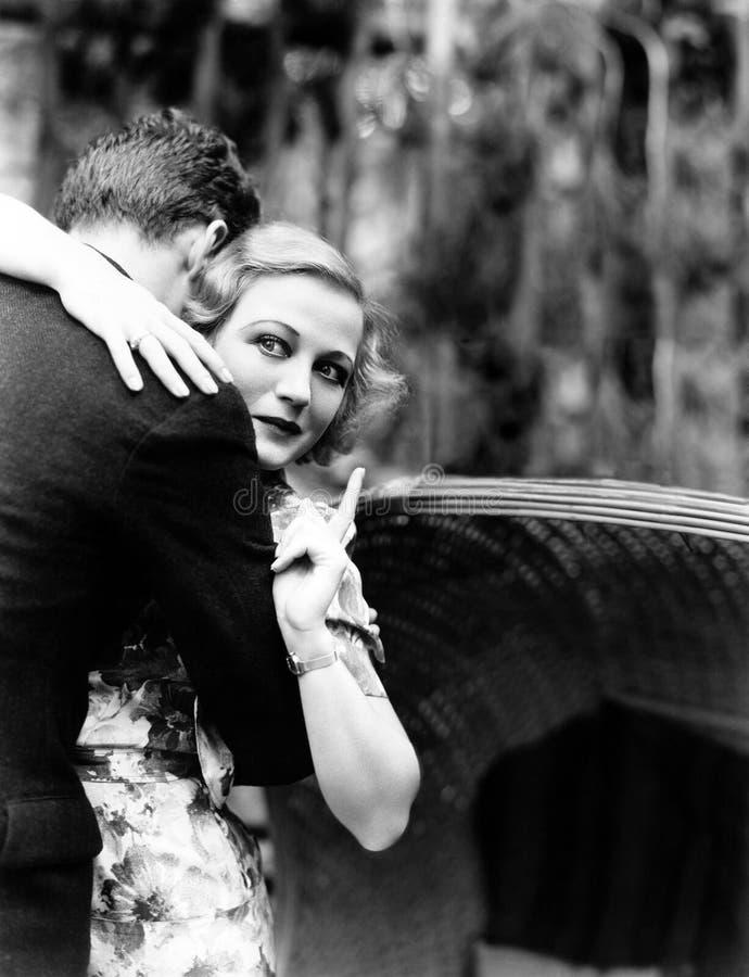 Giovane donna che abbraccia un uomo e che indica verso un bordo di informazioni (tutte le persone rappresentate non sono vivente  immagine stock libera da diritti