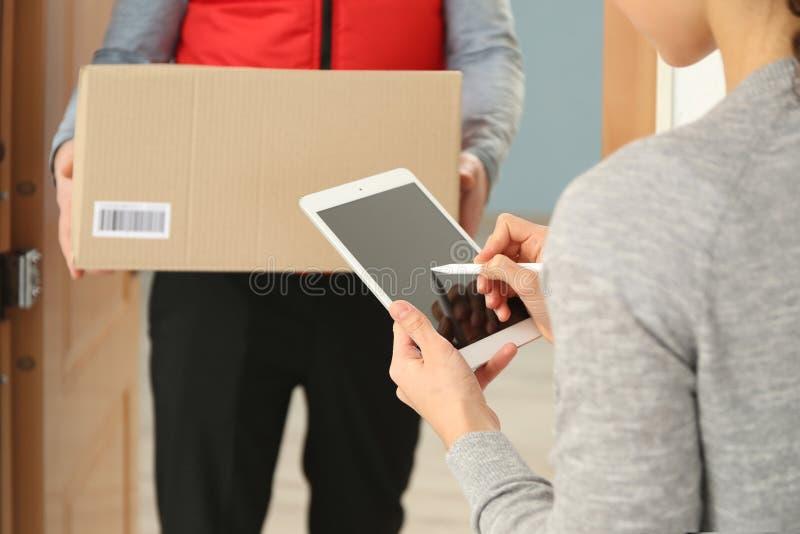 Giovane donna che aggiunge firma dopo la ricezione del pacchetto dal corriere a casa immagini stock libere da diritti