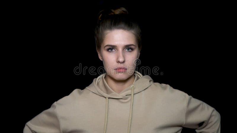 Giovane donna che aggrotta le sopracciglia sopra il fondo nero Donna arrabbiata su fondo nero con il fronte aggrottante le soprac fotografia stock