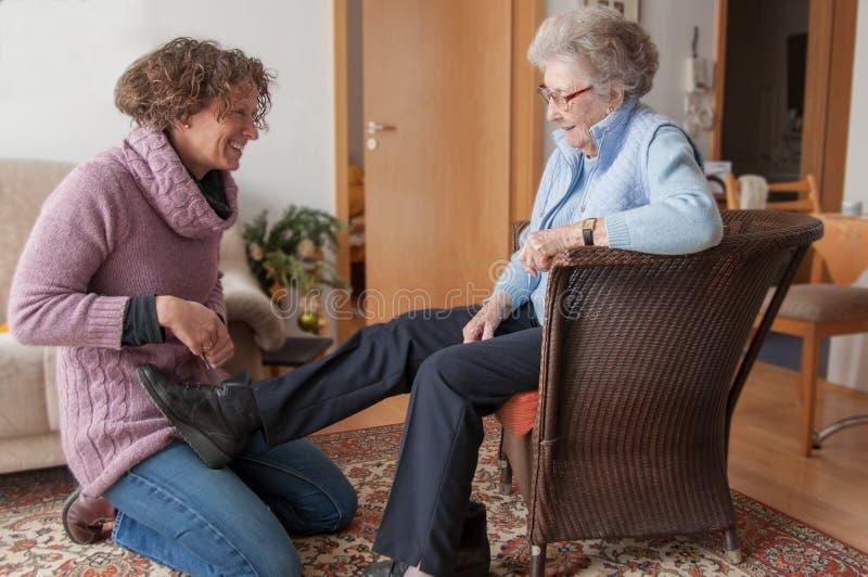 Giovane donna che aiuta signora senior che intraprende le sue scarpe immagini stock libere da diritti