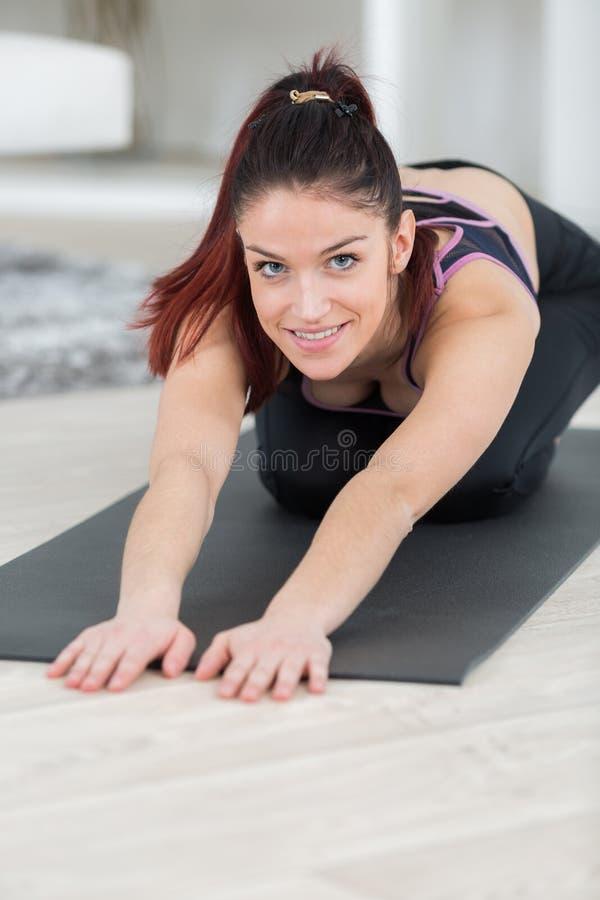 Giovane donna che allunga le gambe a casa fotografie stock libere da diritti