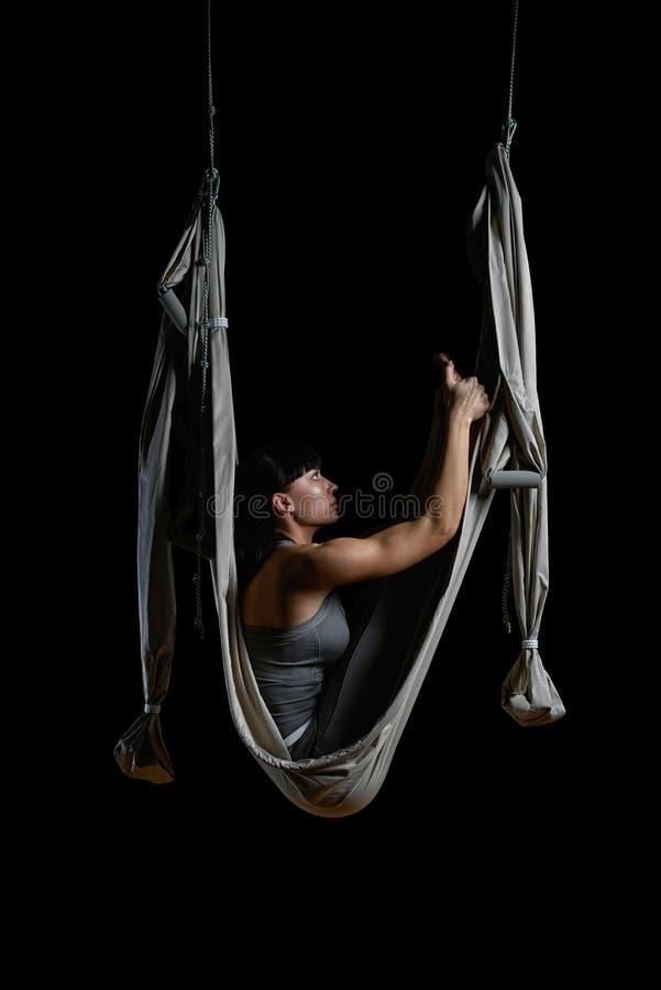 Giovane donna che allunga mentre facendo yoga aerea antigravità fotografie stock