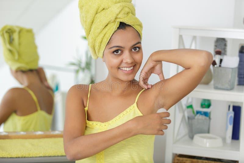 Giovane donna che applica deodorante a sfera fotografia stock libera da diritti