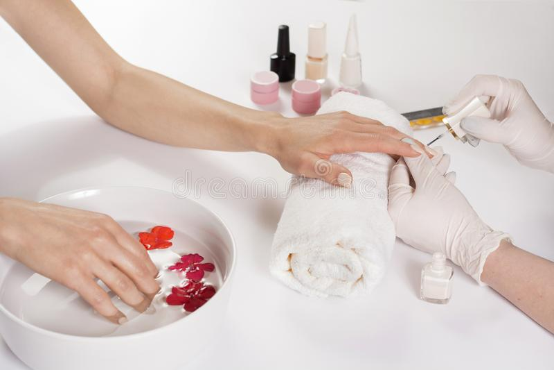 Giovane donna che applica la lucidatura di unghie nel salone professionale del manicure immagine stock libera da diritti