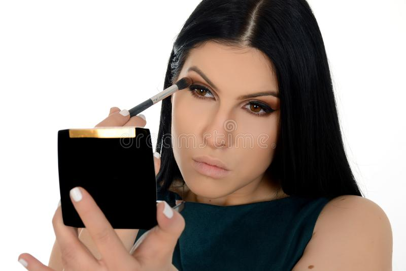Giovane donna che applica la polvere dell'ombretto, tenente piccolo specchio fotografia stock