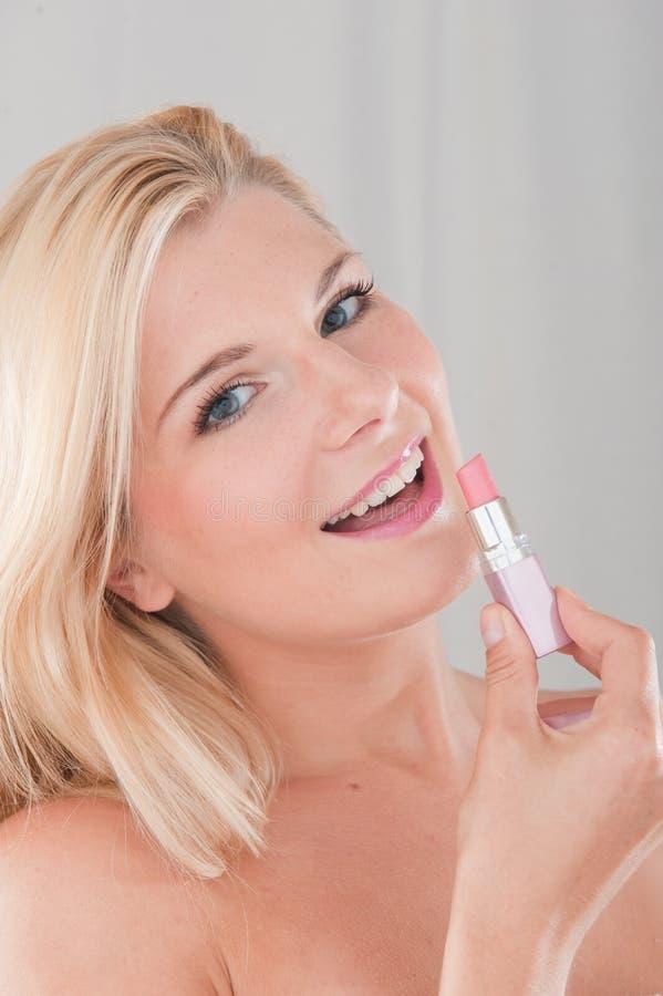 Giovane donna che applica rossetto immagini stock