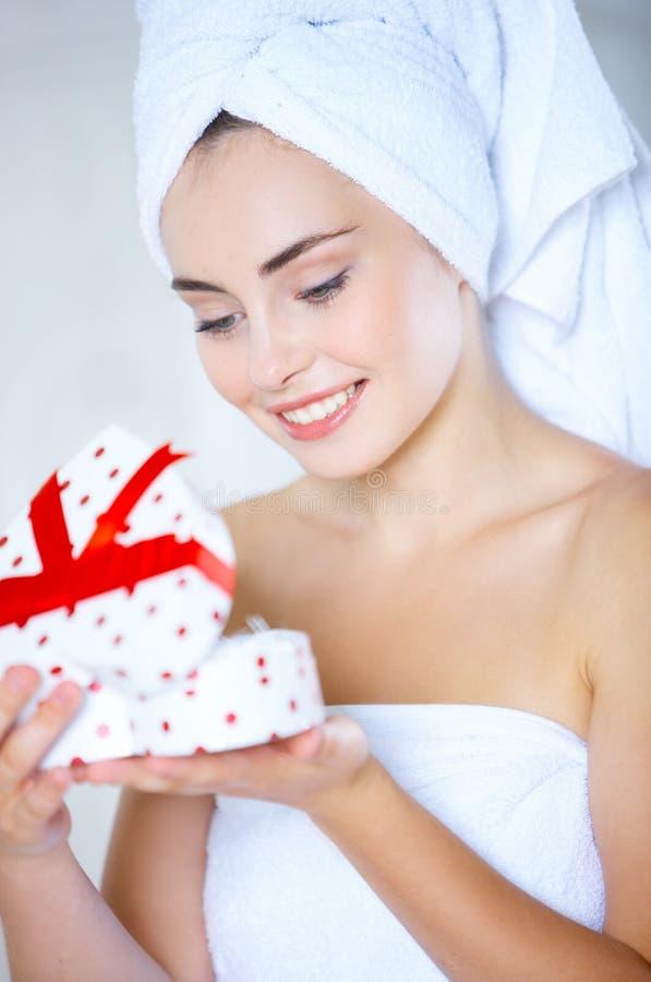Giovane donna che apre un contenitore di regalo in forma di cuore fotografia stock libera da diritti
