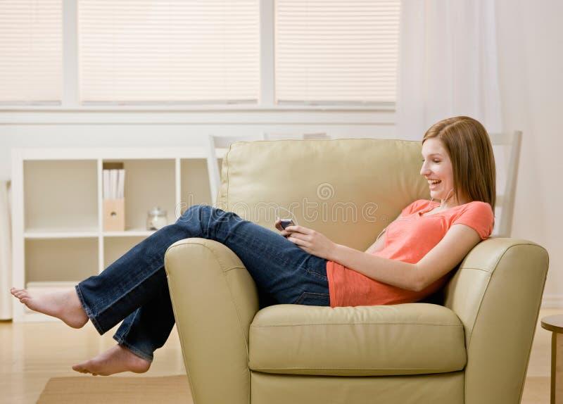 Giovane donna che ascolta il giocatore mp3 sulla poltrona