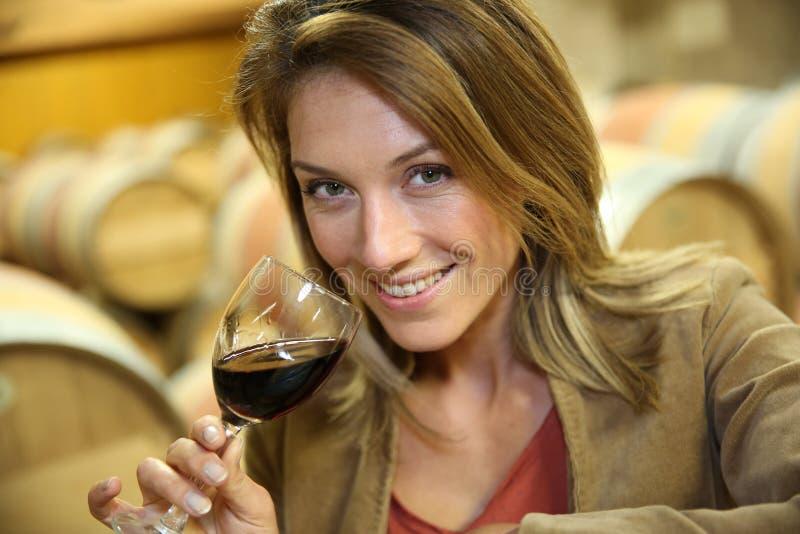Giovane donna che assaggia vino rosso in cantina fotografia stock libera da diritti