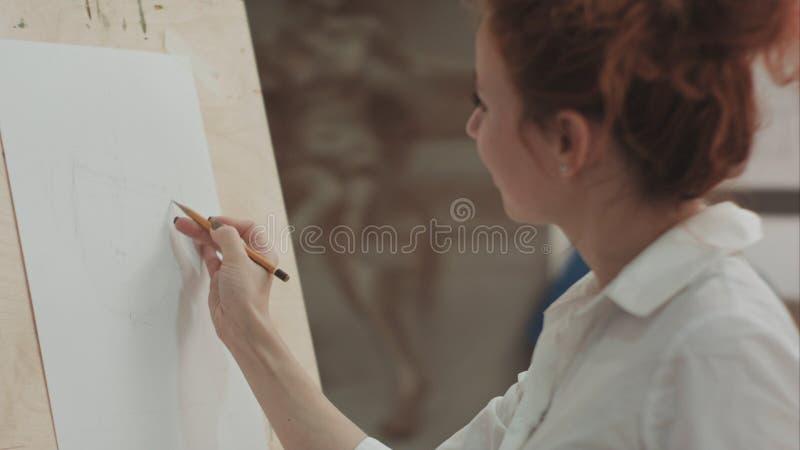 Giovane donna che assorbe matita facendo uso del cavalletto e che spiega il processo fotografia stock