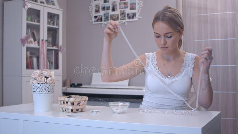 Giovane donna che attacca nastro ai gioielli fatti a mano fotografia stock