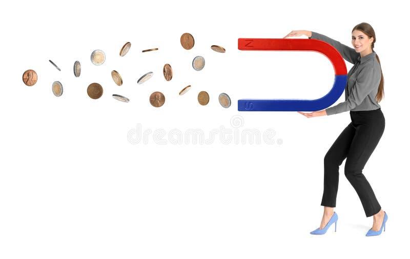 Giovane donna che attira soldi con il magnete su bianco immagine stock libera da diritti