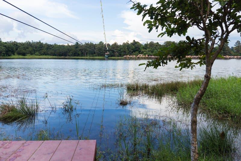 Giovane donna che attraversa un lago nella linea dello zip in Chiang Mai immagini stock libere da diritti