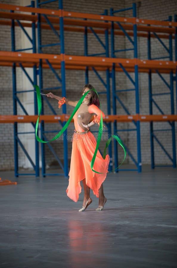 Giovane donna che balla con il nastro relativo alla ginnastica in mani nel magazzino fotografia stock libera da diritti