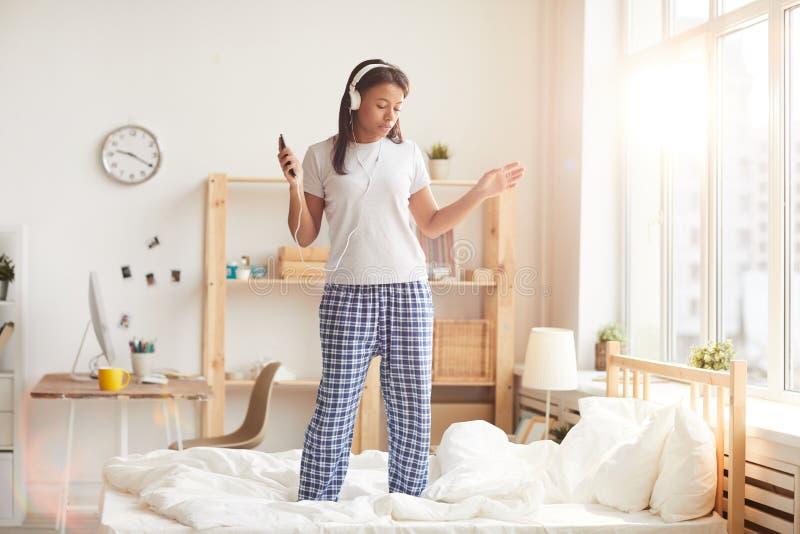 Giovane donna che balla sul letto fotografia stock
