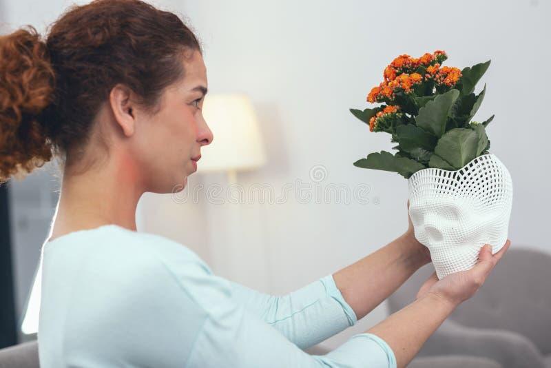 Giovane donna che beholding il vaso di fiore luminoso immagine stock