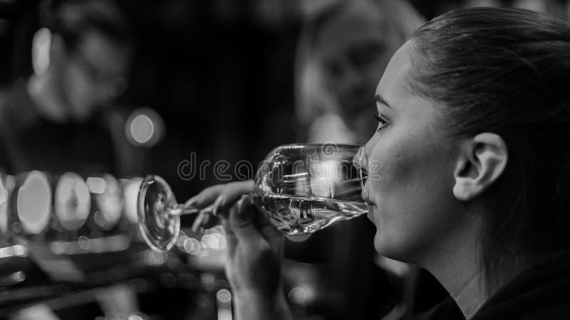 Giovane donna che beve il champagne di vetro di g fotografie stock